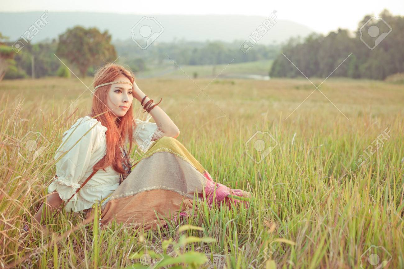 Country hippie girl sitting at golden field - 25222064