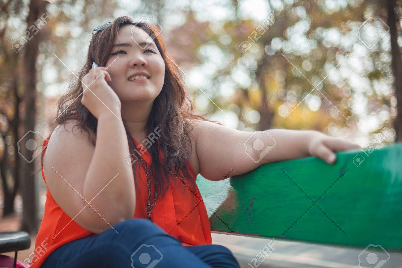 Happy fatty asian woman using mobile phone outdoor in a park - 26579405