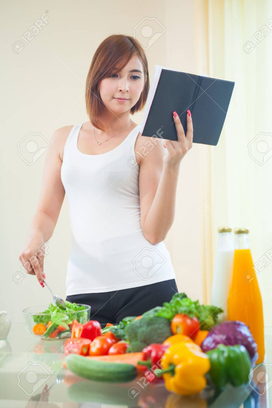 Young asian woman reads cookbook for recipe at kitchen Stock Photo - 28173453