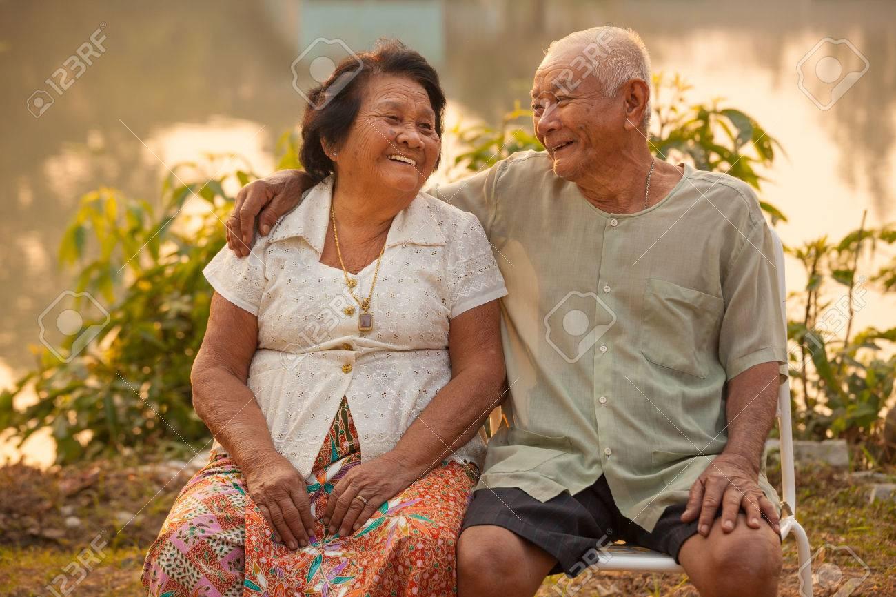 Happy Asian Senior couple sitting outdoors on sunset - 30827211