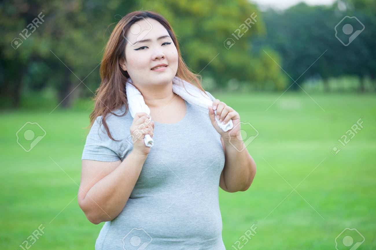 Happy fatty asian fit woman posing outdoor in a park - 34938688