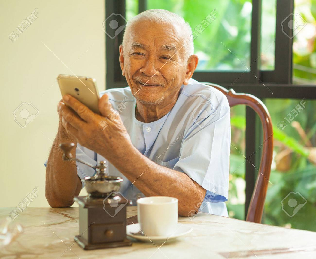 Happy asian senior man using the mobile phone in home - 38168981