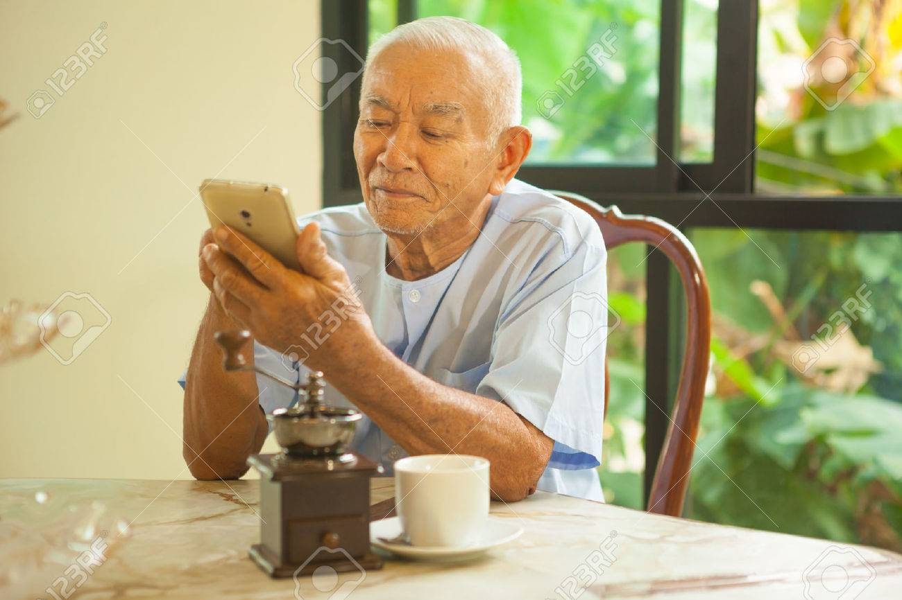 Happy asian senior man using the mobile phone in home - 39304838