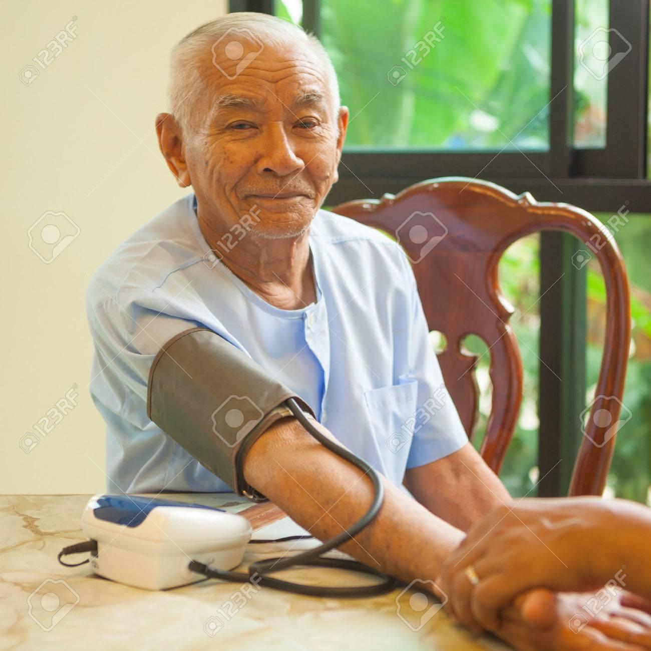 doctor measuring blood pressure of senior asian man patient - 39304867