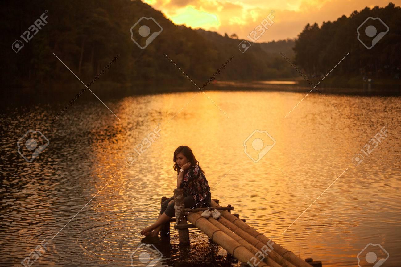 Woman sitting on a pier watching a stunning sunset - 55211418