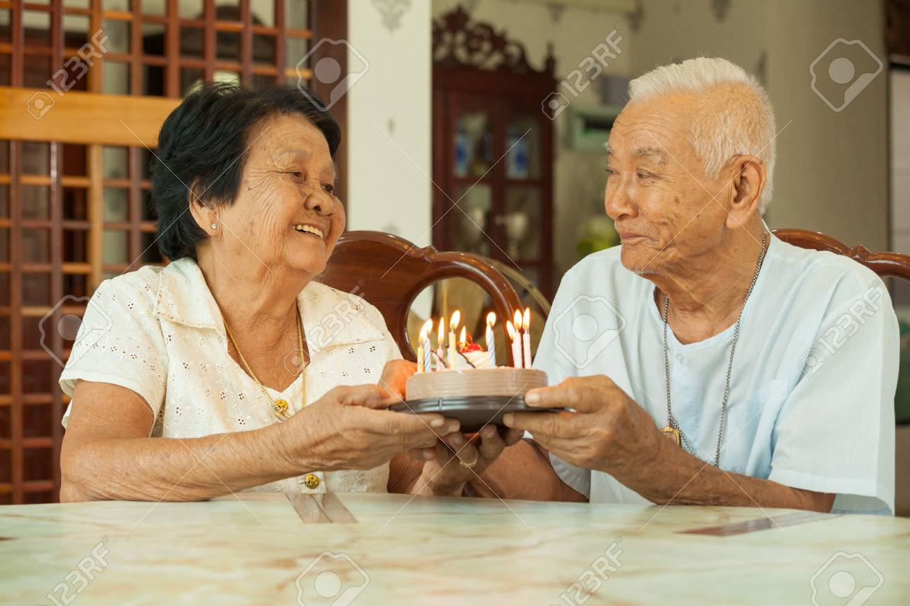Asian senior couple holding a cake and smiling in living room - 60396802