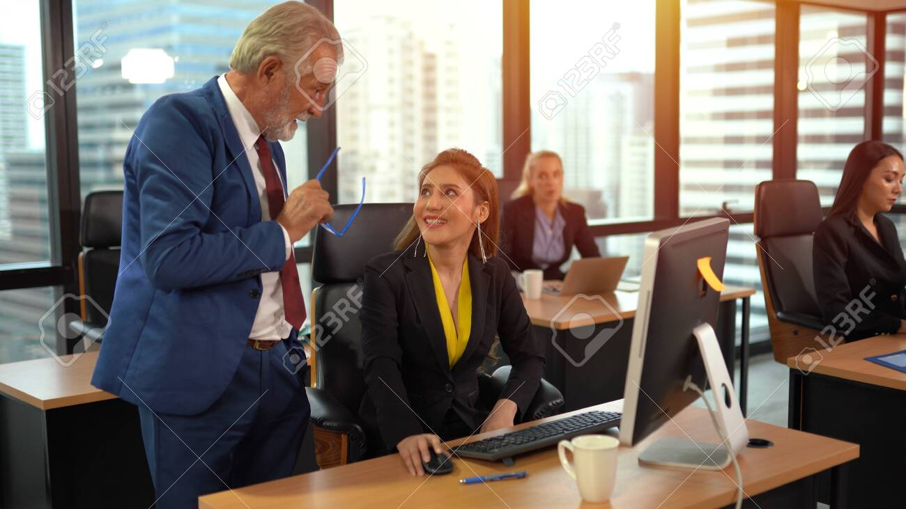 Smiling senior employee discussing with business woman at workplace - 134715940