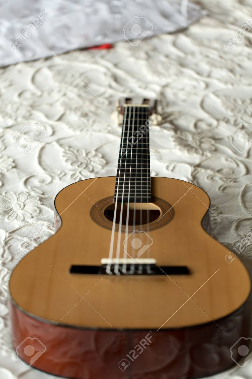 Spanish Guitar Lying On The Bed Stock Photo Picture And Royalty