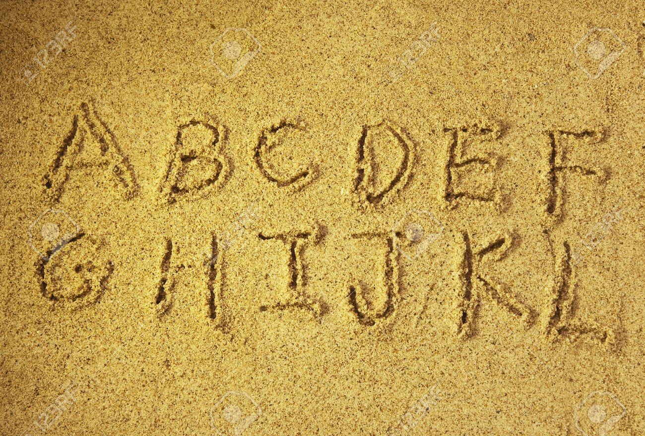 stock photo alphabet letters handwritten in sand on beach