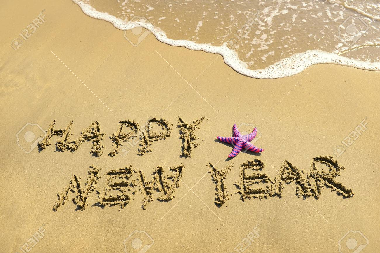 happy new year message on the sand beach stock photo 24730408