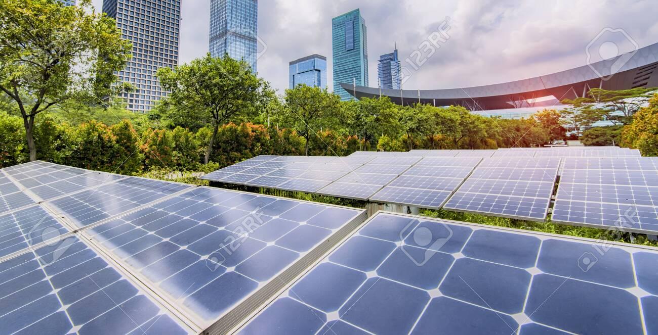Ecological energy renewable solar panel plant with urban landscape - 128944325