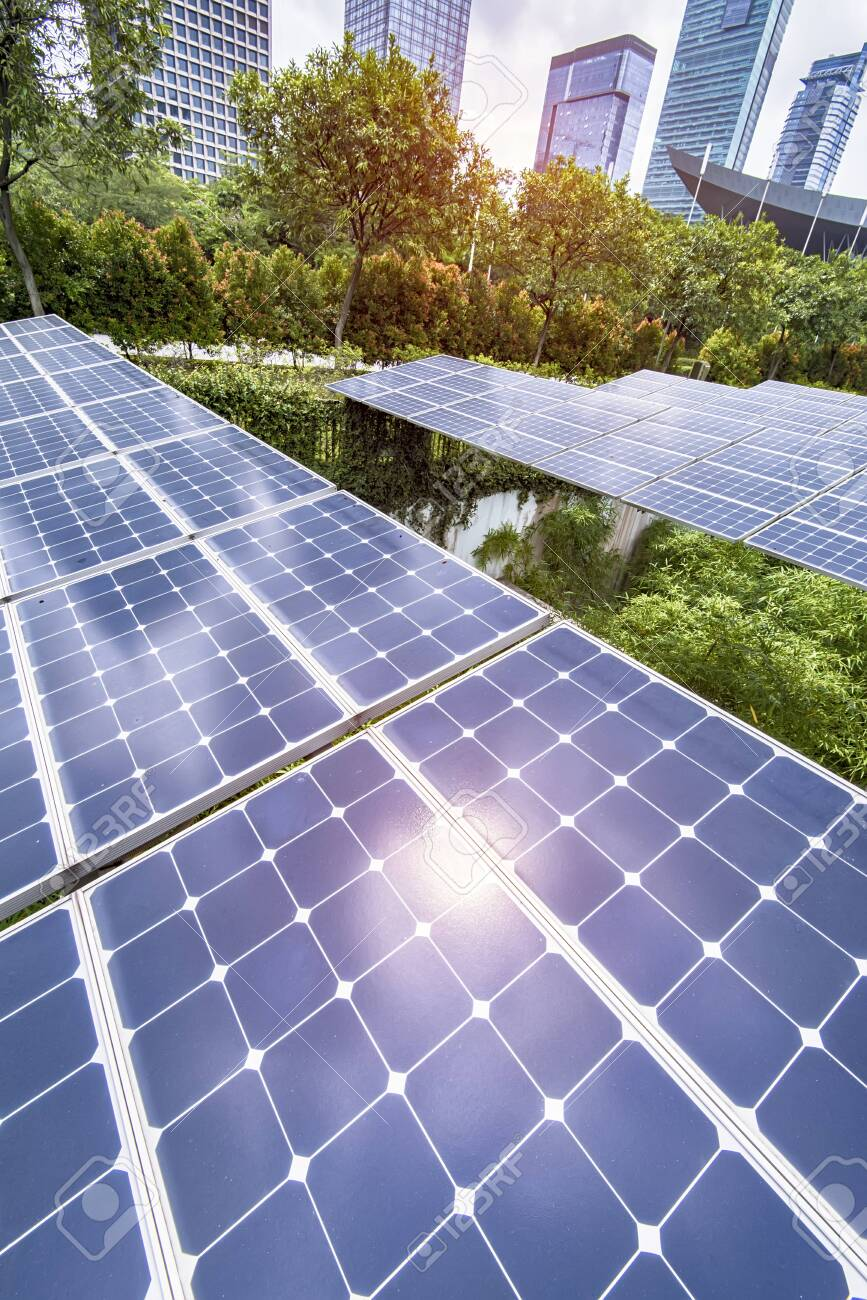 Ecological energy renewable solar panel plant with urban landscape - 128944342