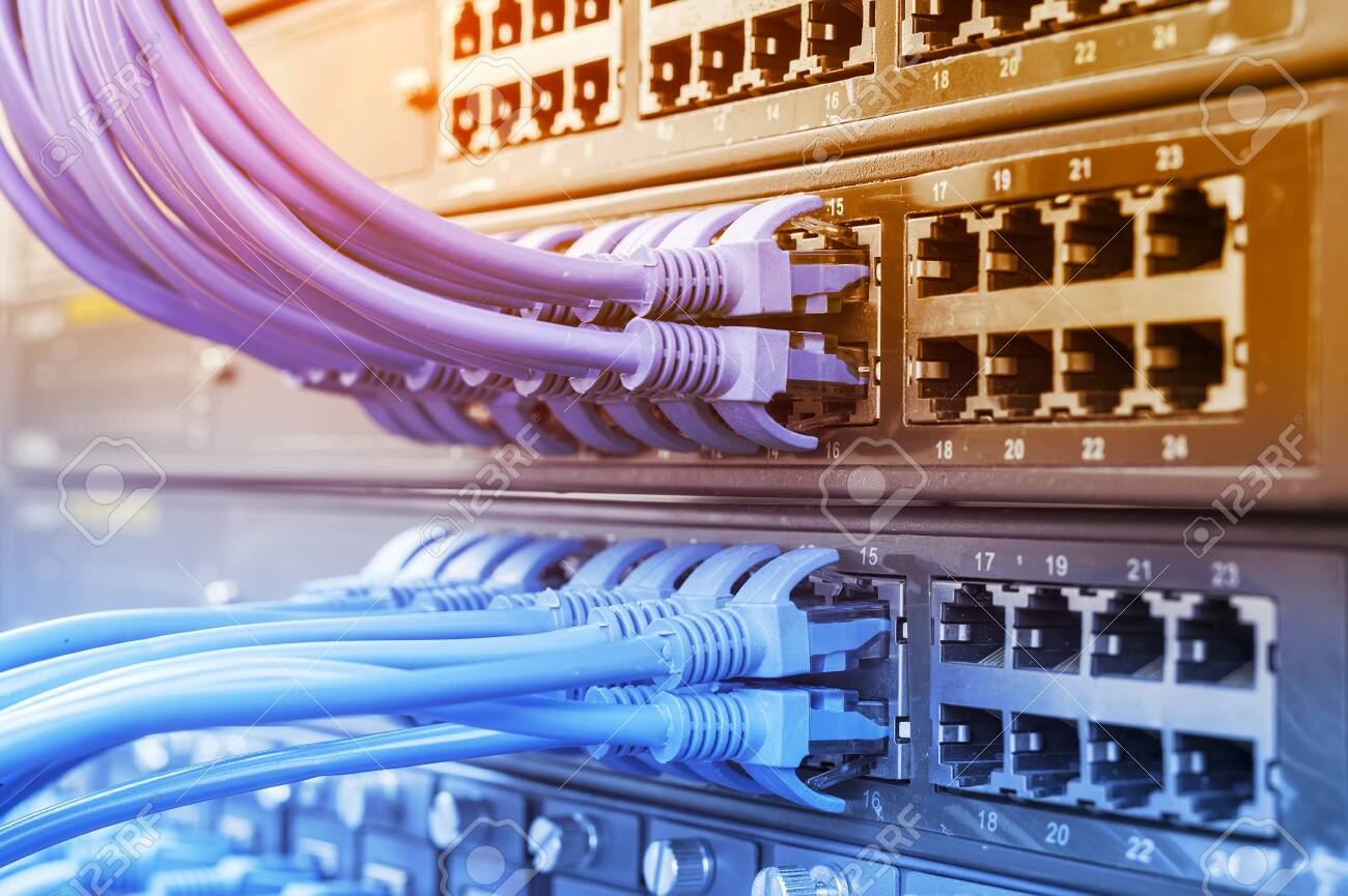 Server rack with blue and red internet patch cord cables connected to black patch panel in data server room - 137128730