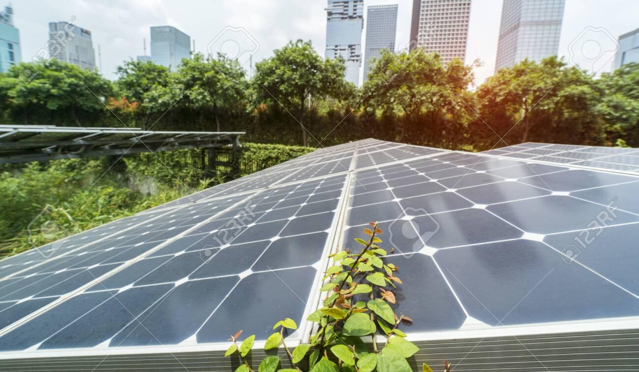 Ecological energy renewable solar panel plant with urban landscape landmarks - 148775192