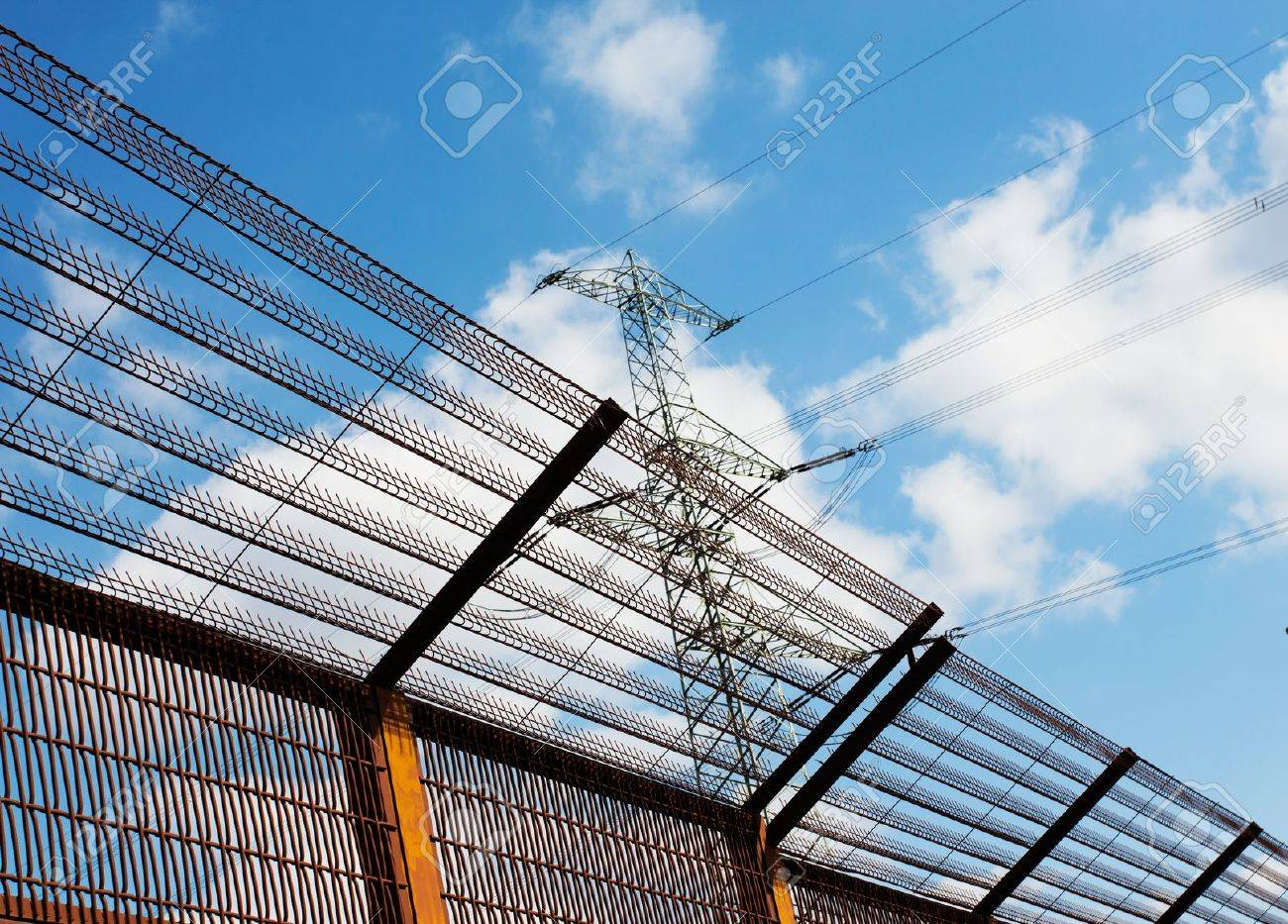 Barrier fence and Electricity pylon against the blue sky - 21359904