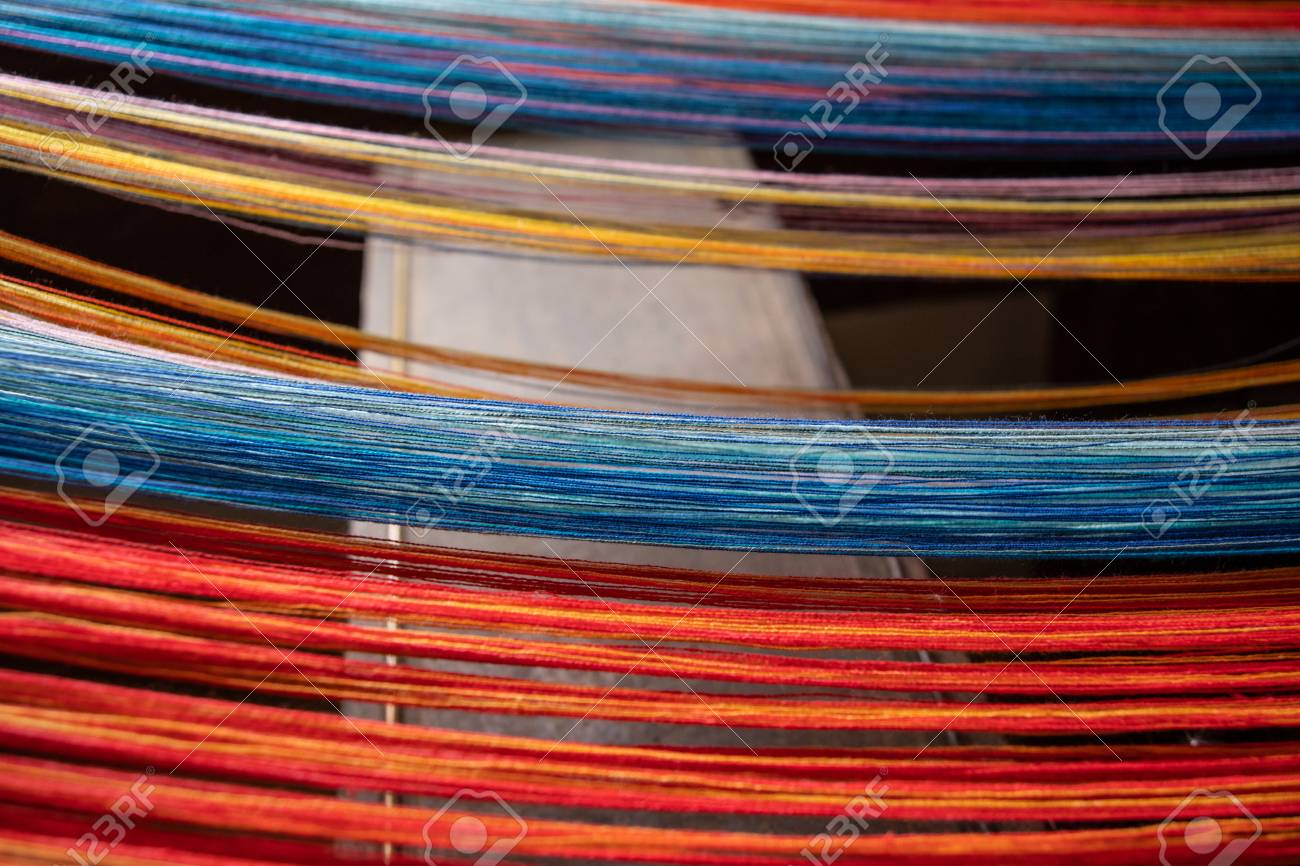 Colored threads of an ancient wooden loom . - 117911228