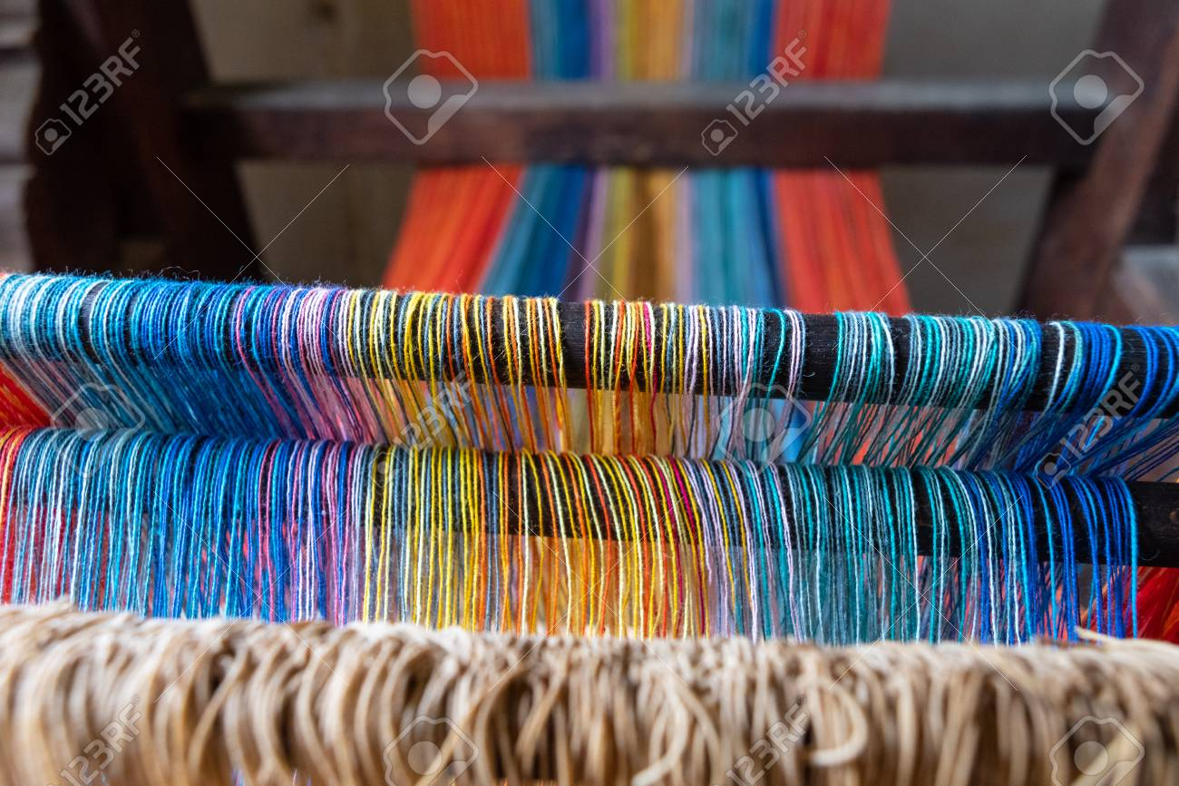 Colored threads of an ancient wooden loom . - 117911424