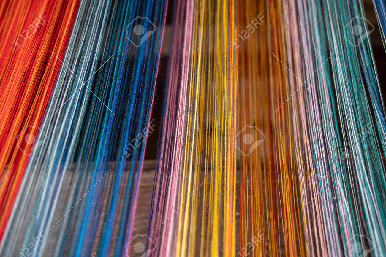 Colored threads of an ancient wooden loom . - 117911816