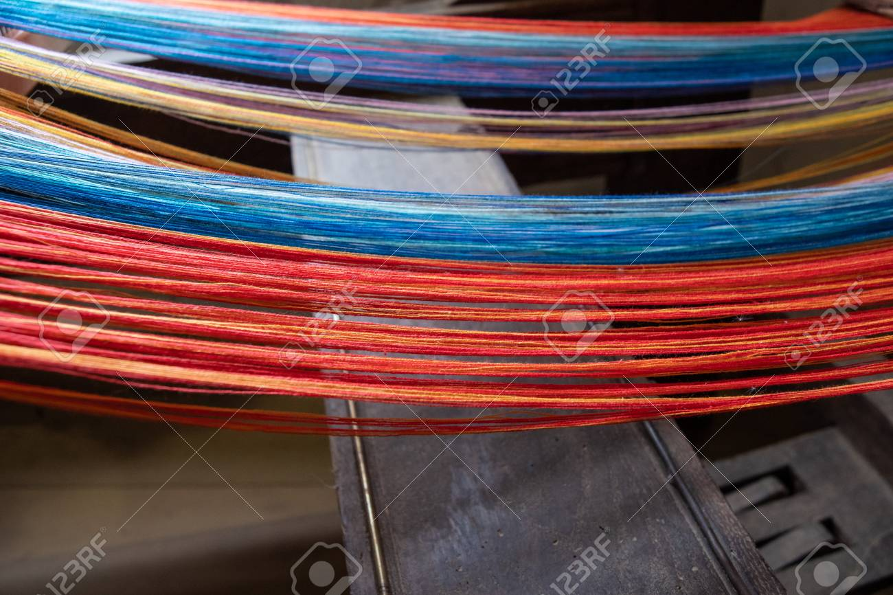 Colored threads of an ancient wooden loom . - 117911825