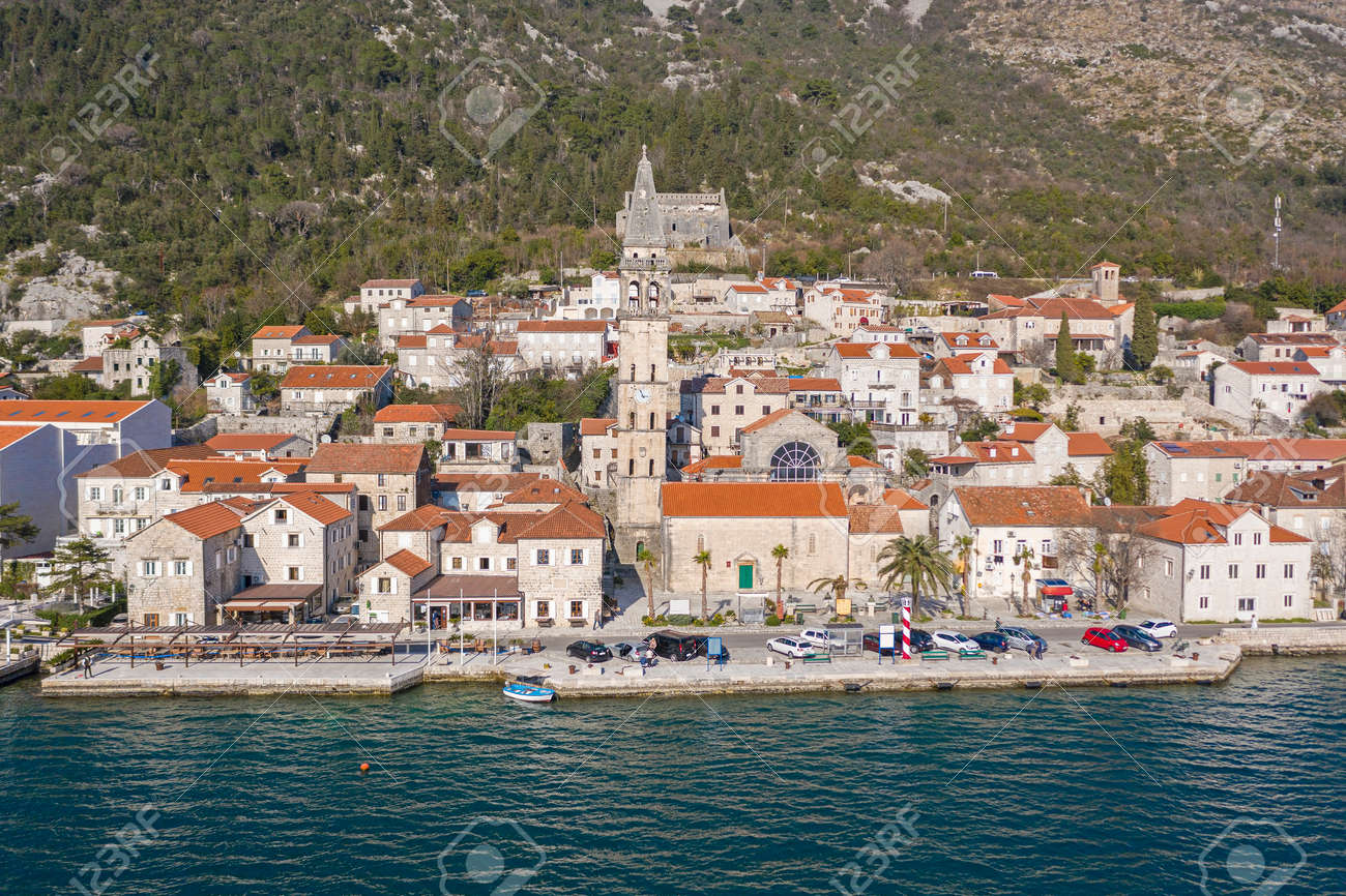 Aerial shot of the old coastal town of Perast at the foot of the mountain. Seaside promenade, residential buildings with traditional balkan red roofs, ancient Cathedral and coastline - 165655001