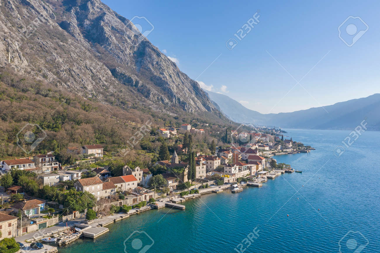 Aerial shot of the old coastal town of Perast at the foot of the mountain. Seaside promenade, residential buildings with traditional balkan red roofs, ancient Cathedral and coastline - 165655003