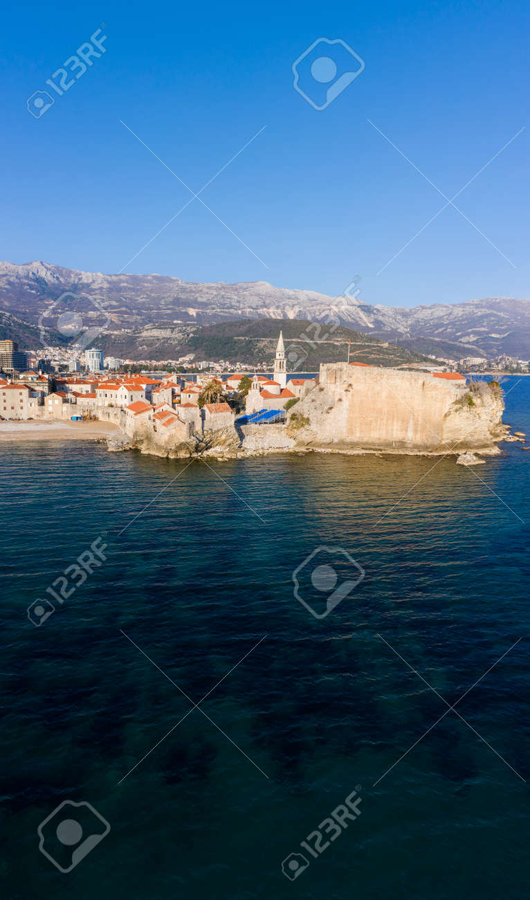 Aerial View of Budva Old Town and sandy beach in a beautiful spring day. Top view from drone on the old fortress and azure sea. Vertical panorama, Montenegro - 165655013