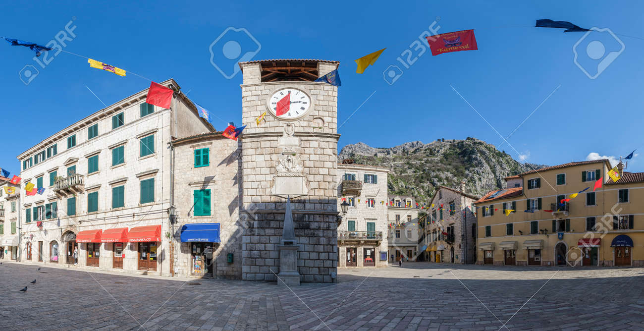 Panorama of the Old Town of Kotor, ancient square with a clock tower in the traditional Balkan architectural style with a cobblestone pavement on a sunny spring day. Mountains are visible on the backg - 165773093
