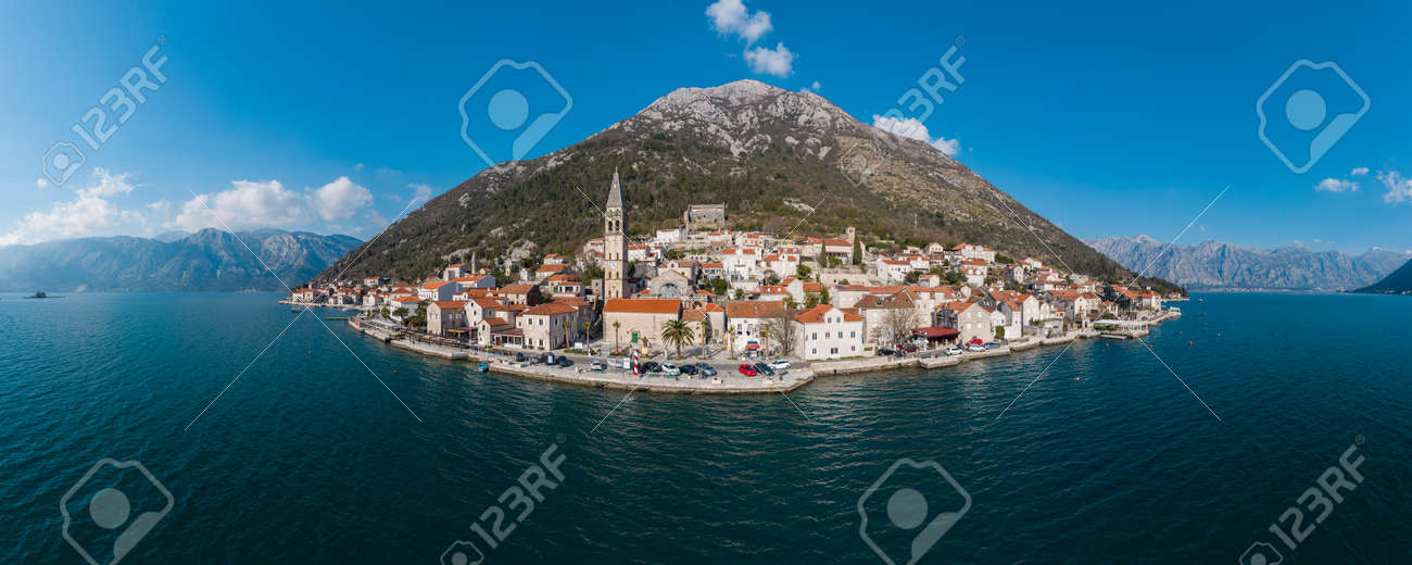 Panorama bird's eye view of small island in Adriatic sea, covered by greenery, traditional Balkan style architecture, ancient buildings and cathedral. Mountains in the background - 166666245