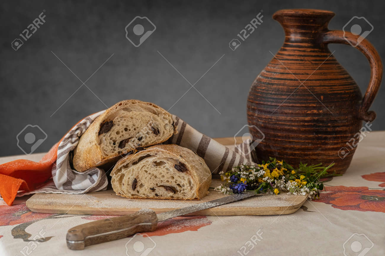 Still life, food photography - close-up of fresh sliced white bread on a cutting board on the table, knife, linen towel and little bouquet of wildflowers, a jug of milk in the background - 170377729