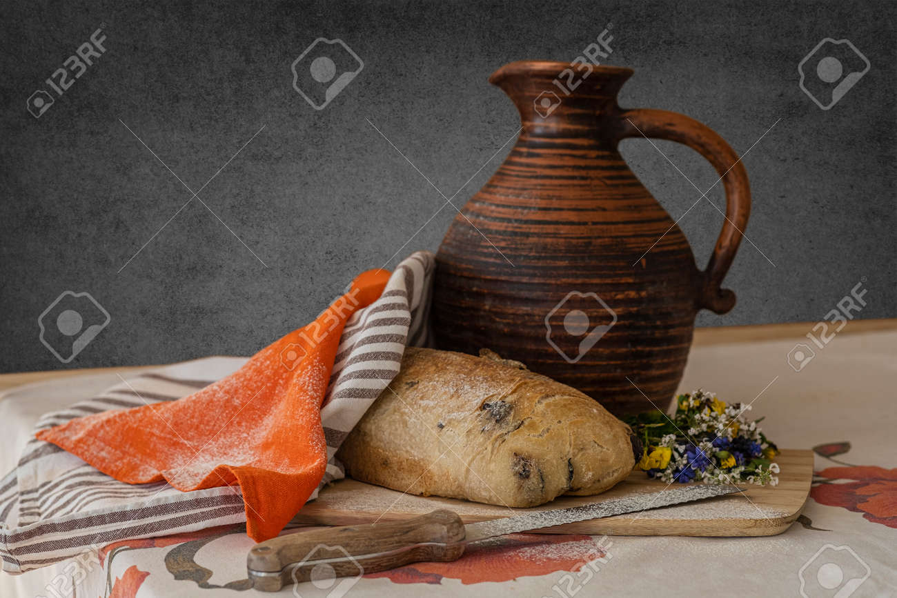 Still life, food photography - close-up of fresh sliced white bread on a cutting board on the table, knife, linen towel and little bouquet of wildflowers, a jug of milk in the background - 170377733