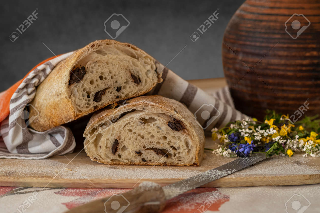 Still life, food photography - close-up of fresh sliced white bread on a cutting board on the table, knife, linen towel and little bouquet of wildflowers, a jug of milk in the background - 170377735
