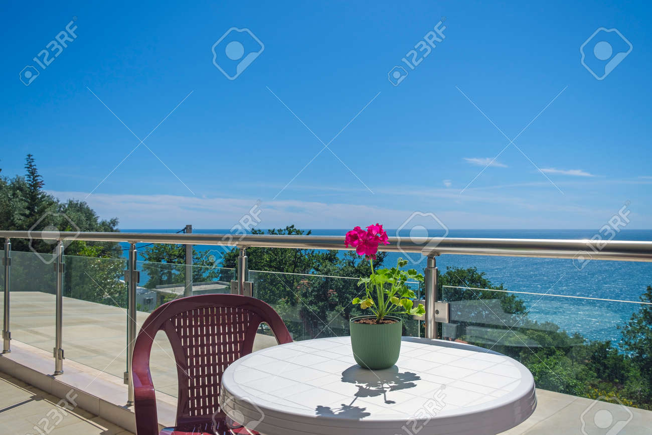 Spacious terrace in the private villa with sea view. The terrace offers view on the sea and coastline, covered by greenery. On the terrace there is a plastic table with a chair, on the table there is a red flower for decoration - 170377744