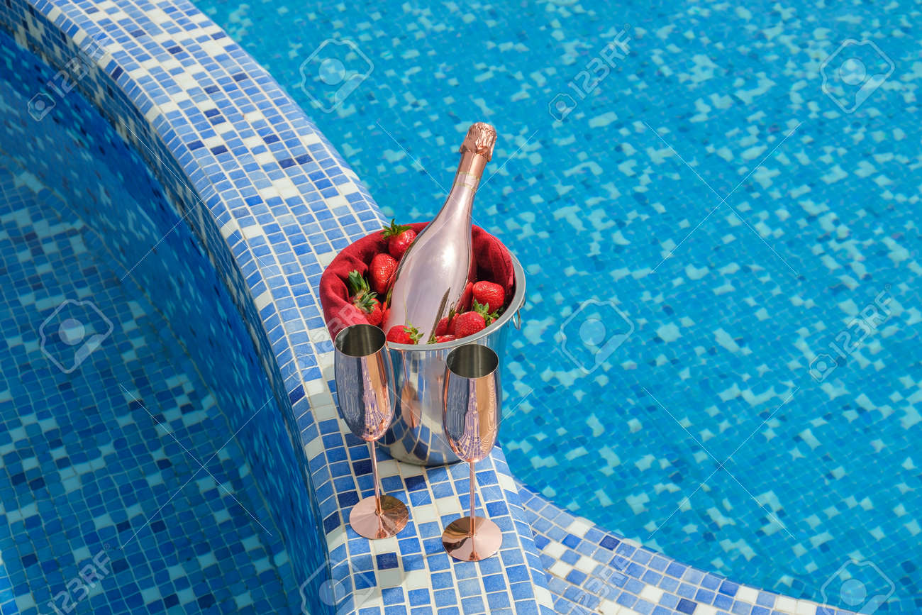 Swimming pool view. Close-up of a bucket with champagne, strawberries and two empty glasses on the side of the pool - 170377748