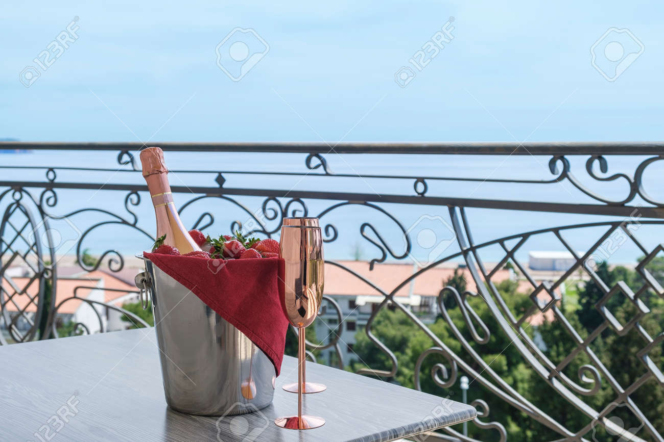 Served table on the terrace of a luxury villa with sea view. On the table are a bucket with champagne, strawberries and two empty glasses. Through the balcony lattice we see the blue sky and the azure sea - 170377753