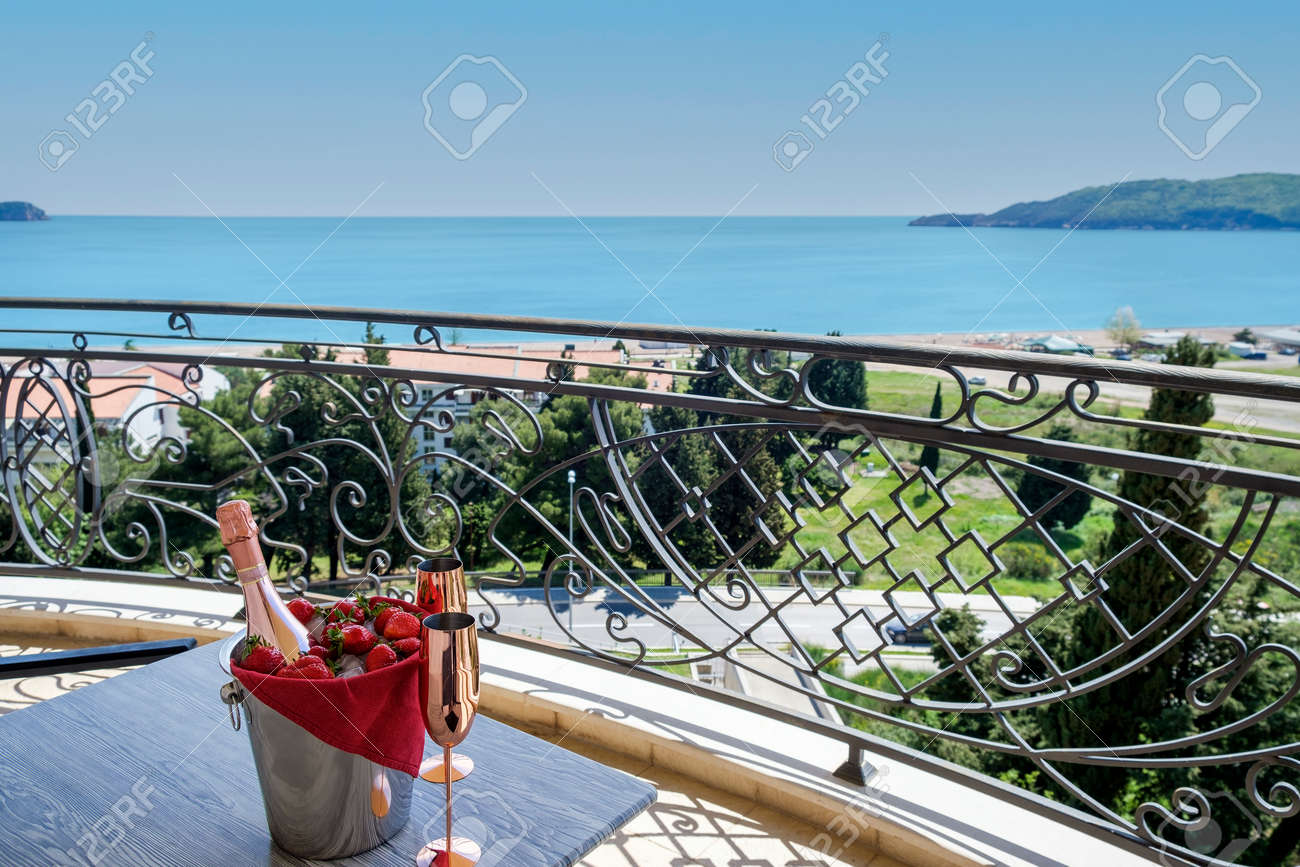 Served table on the terrace of a luxury villa with sea view. On the table are a bucket with champagne, strawberries and two empty glasses. Through the balcony lattice we see the blue sky and the azure sea - 170377765