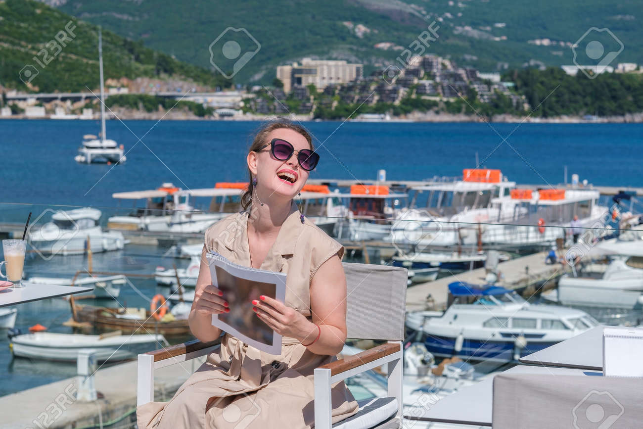 Young pretty European woman in sunglasses with brown hair pulled back is sitting at in a terrace of a summer cafe with sea and marina view and holds a magazine, laughing - 170377767