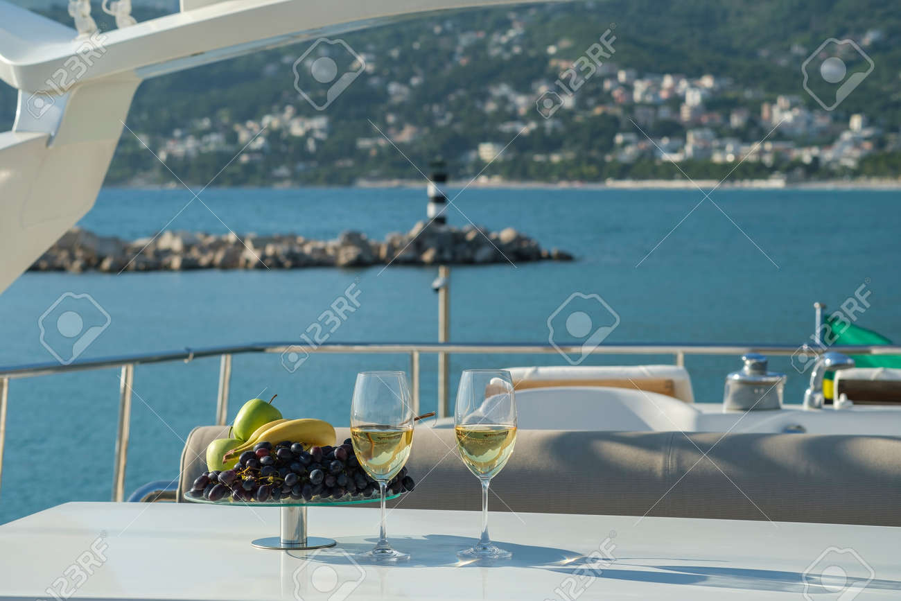 Yacht cruise. A table is set on the deck, there are glasses of white wine and a dish of fruit on the table. The yacht offers a view of the lighthouse and the mountains - 170815744