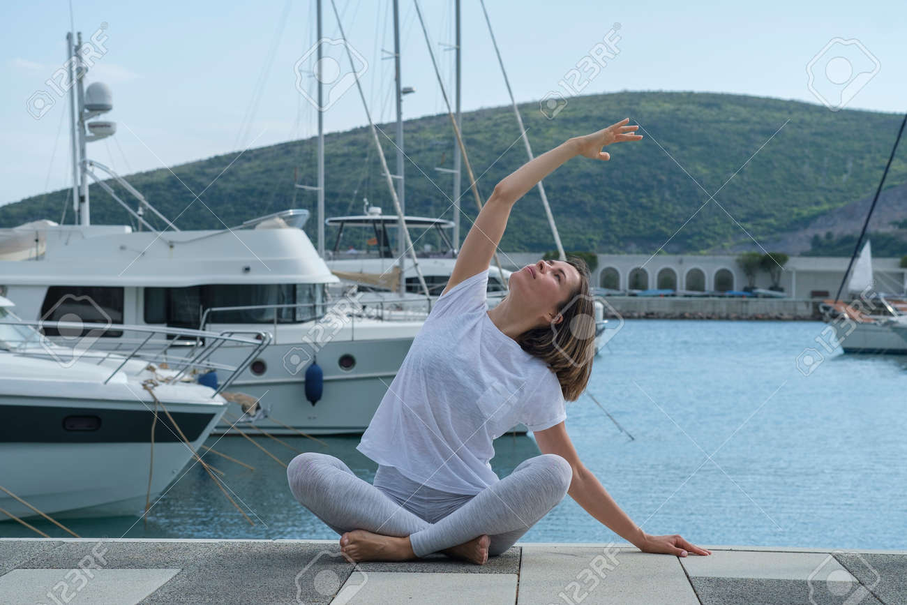 Young slim beautiful woman practicing yoga in the marina, against the background of yachts standing at the pier. Exercising, making yoga pose on the seashore - 171506264