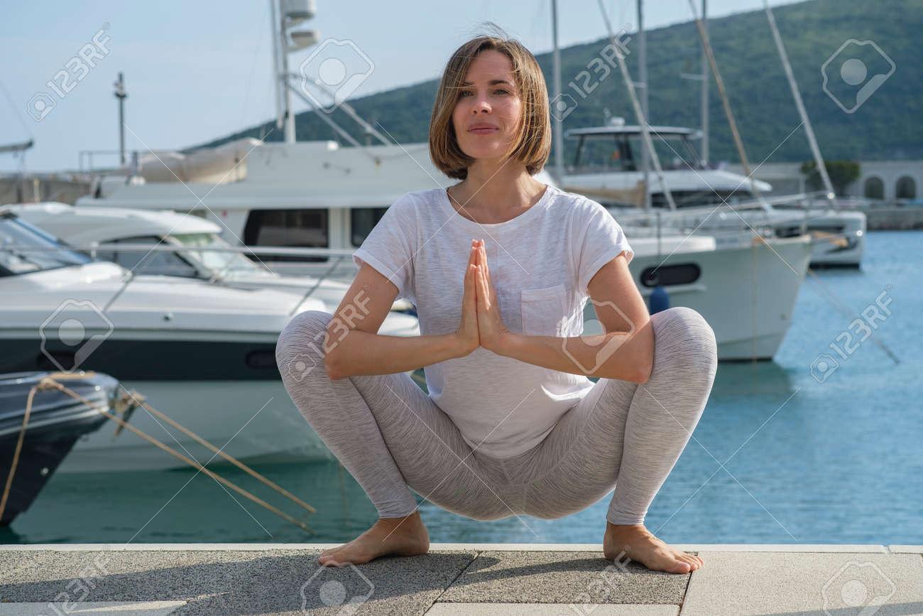 Young slim beautiful woman practicing yoga in the marina, against the background of yachts standing at the pier. Exercising, making yoga pose on the seashore - 171535716