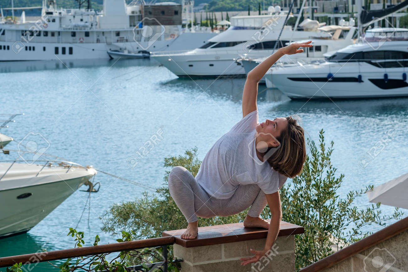 Young slim beautiful woman practicing yoga in the marina, against the background of yachts standing at the pier. Exercising, making yoga pose on the seashore - 171678397