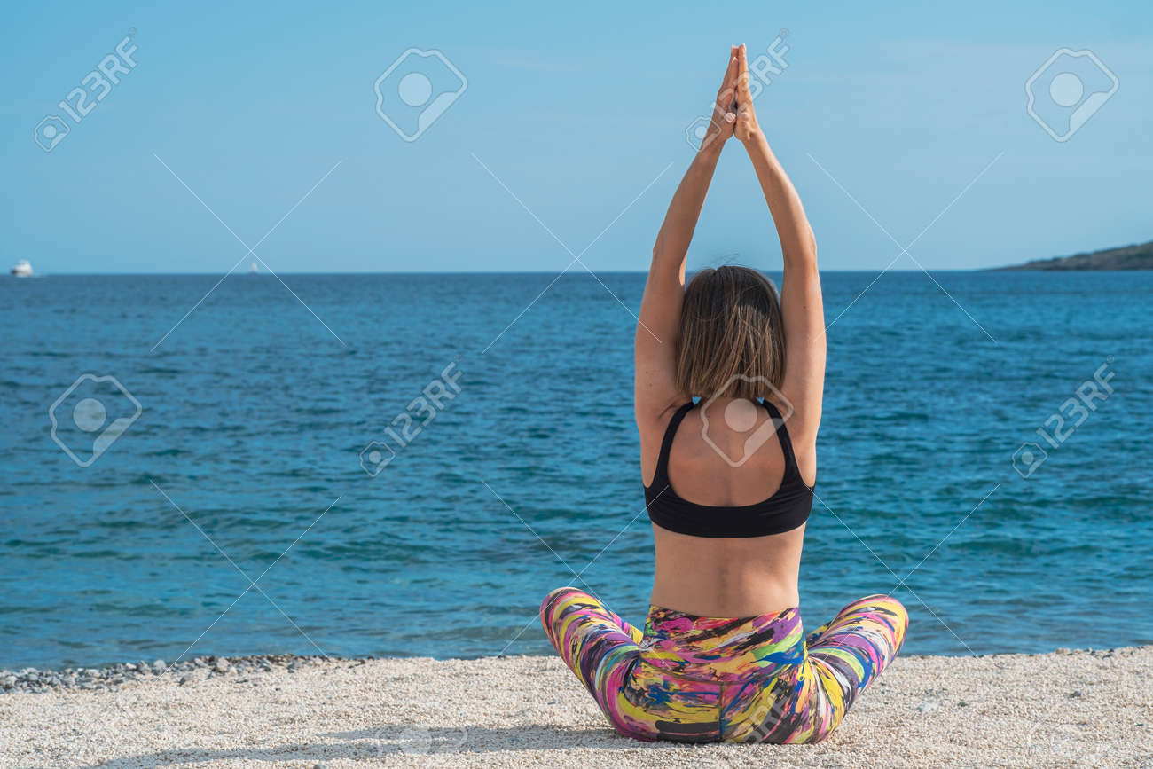 Young slim beautiful woman practicing yoga on the seashore, on the beach, against the background of the sea. Exercising, making yoga pose on the sandy beach. Back view - 171535645