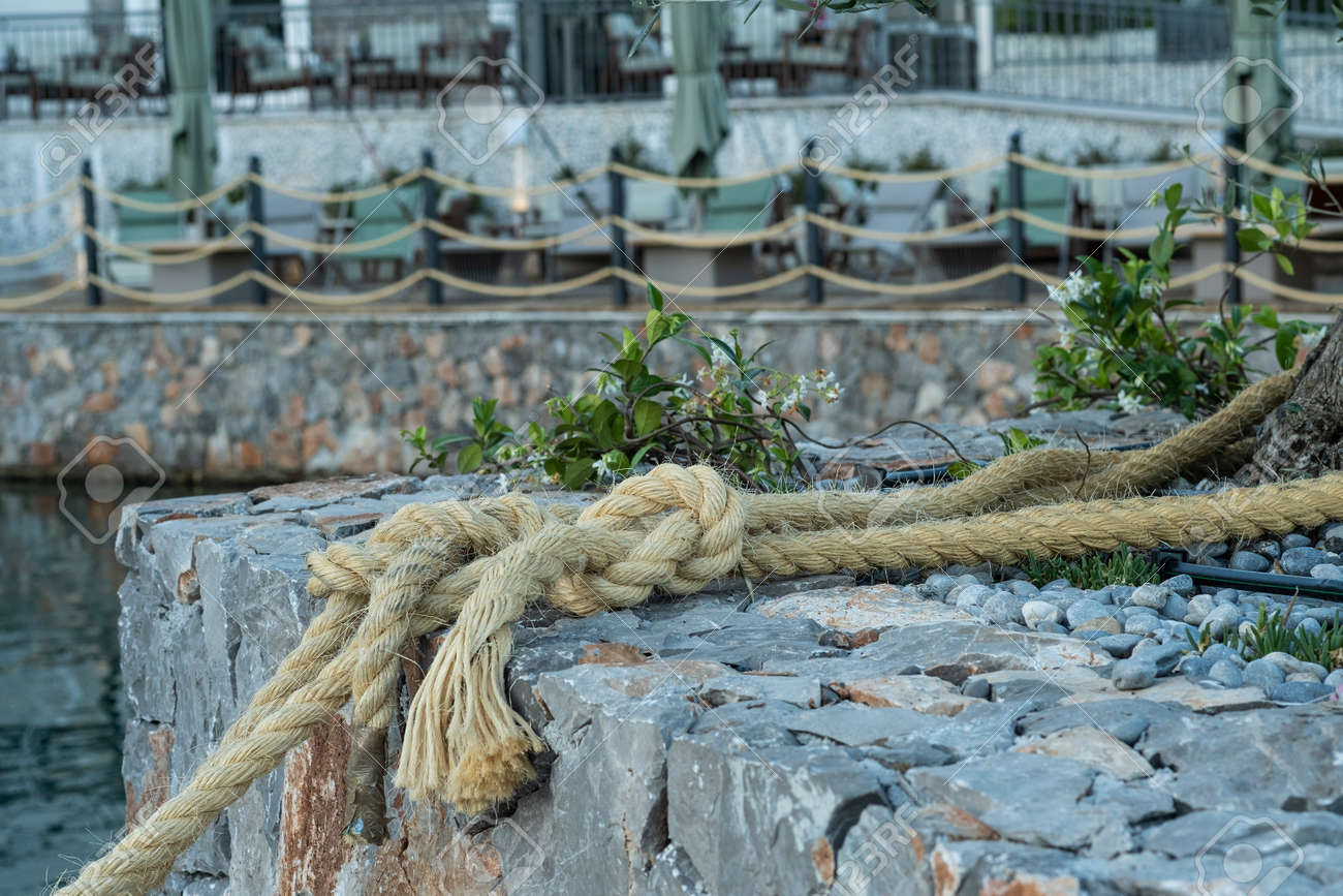 Close-up of a ship's rope as part of the decoration that adorns the embankment of a coastal town. In the background is a cafe on the seashore, tables are in the open air - 171730415