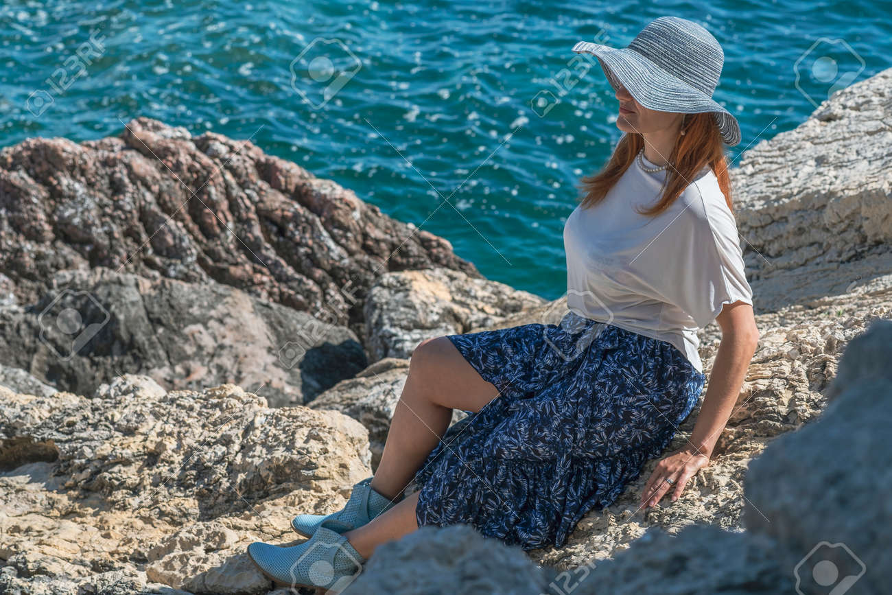 Young woman tourist in a hat, sunglasses, blue skirt and white blouse is sitting on the rocks on the seashore near the water - 171801300
