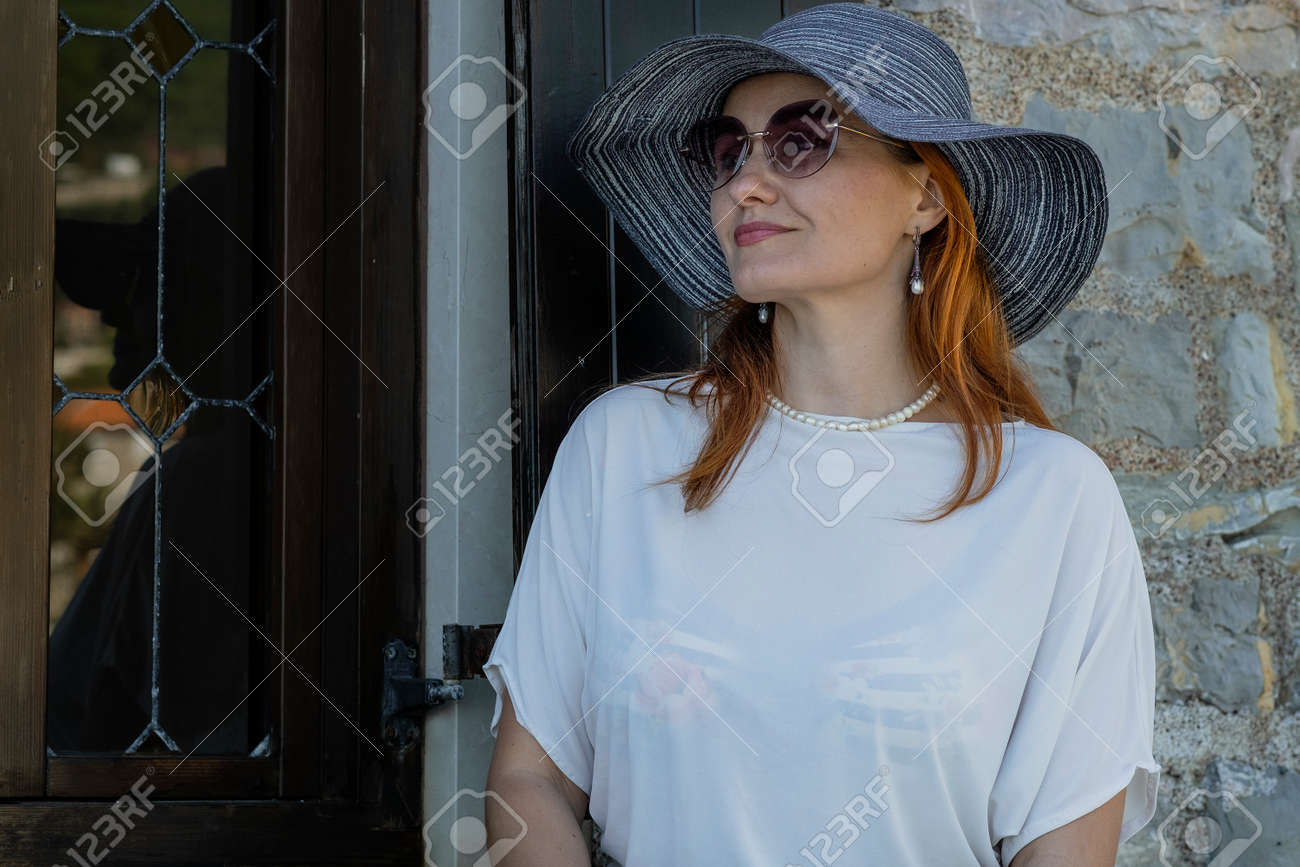 Portrai of a smiling woman tourist in a blue hat, sunglasses and white blouse with long red hair. Cafe entrance is behind her - 171801309