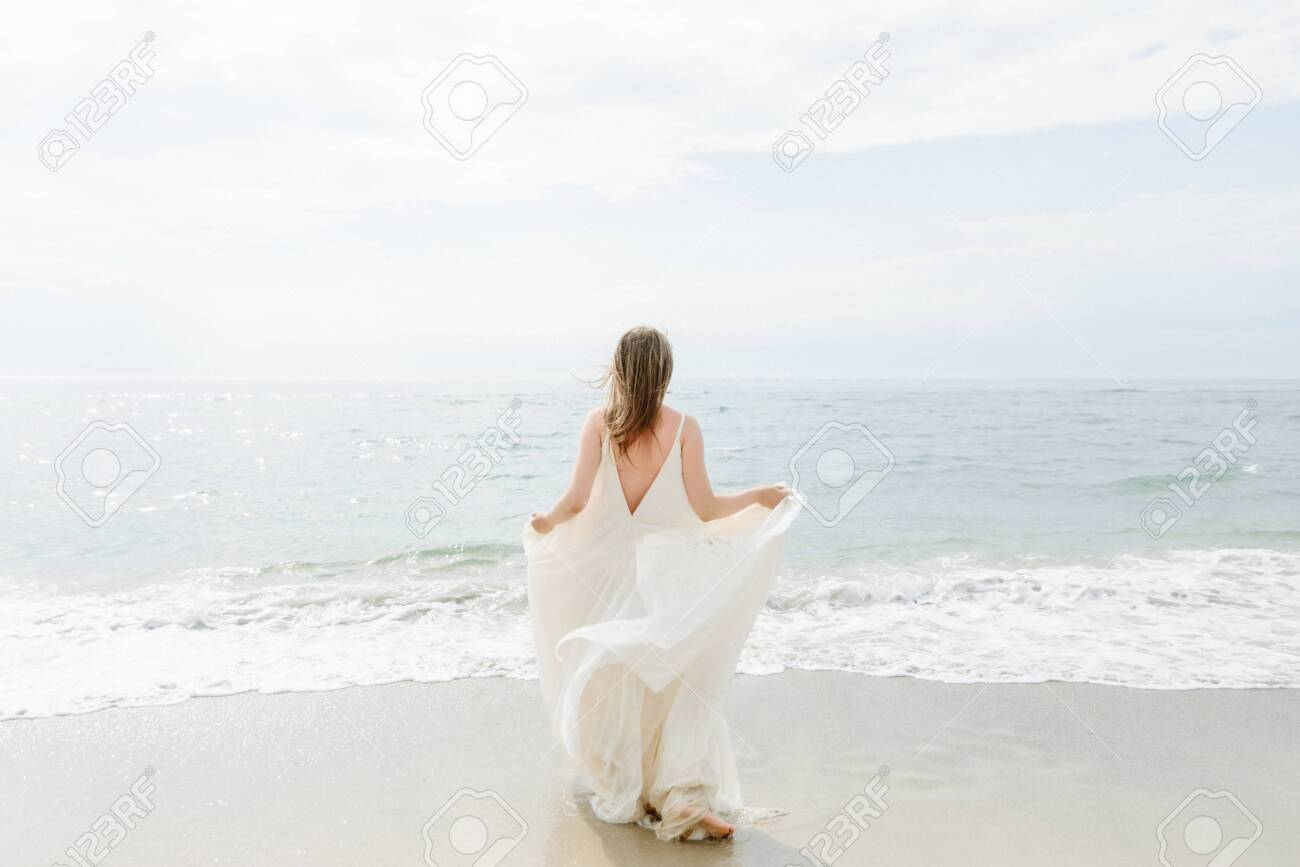 A young beautiful girl in a long milk-colored dress walks along the beach and pier against the background of the sea. - 143416434