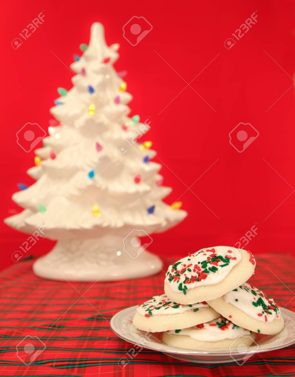 christmas holiday sugar cookies on a red background with a lit up ornamental tree blured in the back Stock Photo - 11536316
