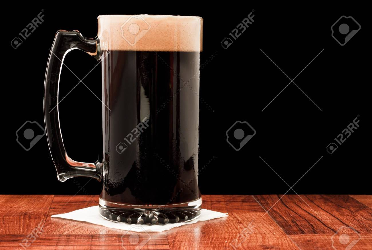 dark beer isolated on a black backgoud served in a chilled mug Stock Photo - 13030794