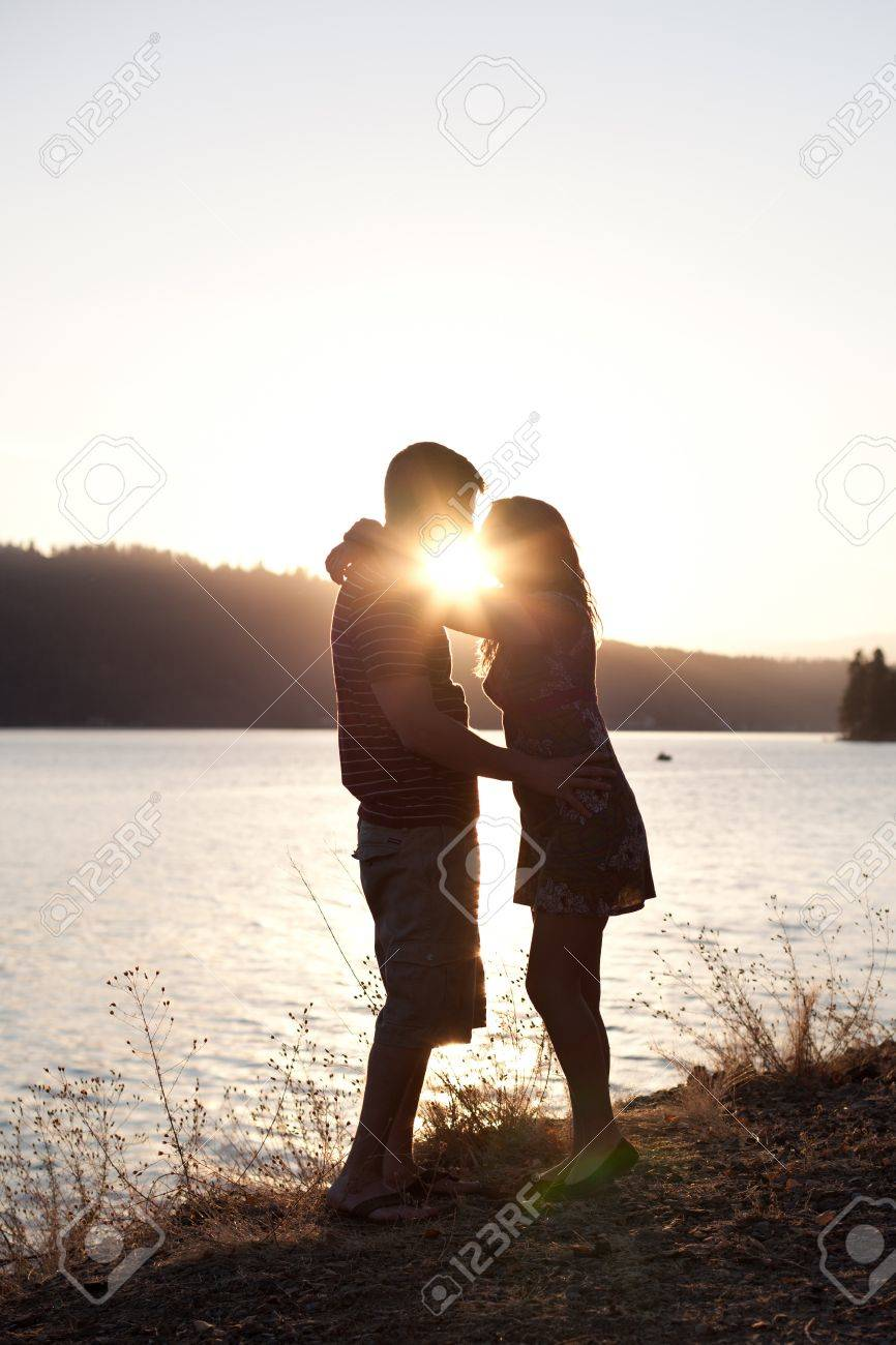 young couple kissing on the shore with the sun behind them, dramatic and low color Stock Photo - 15773846