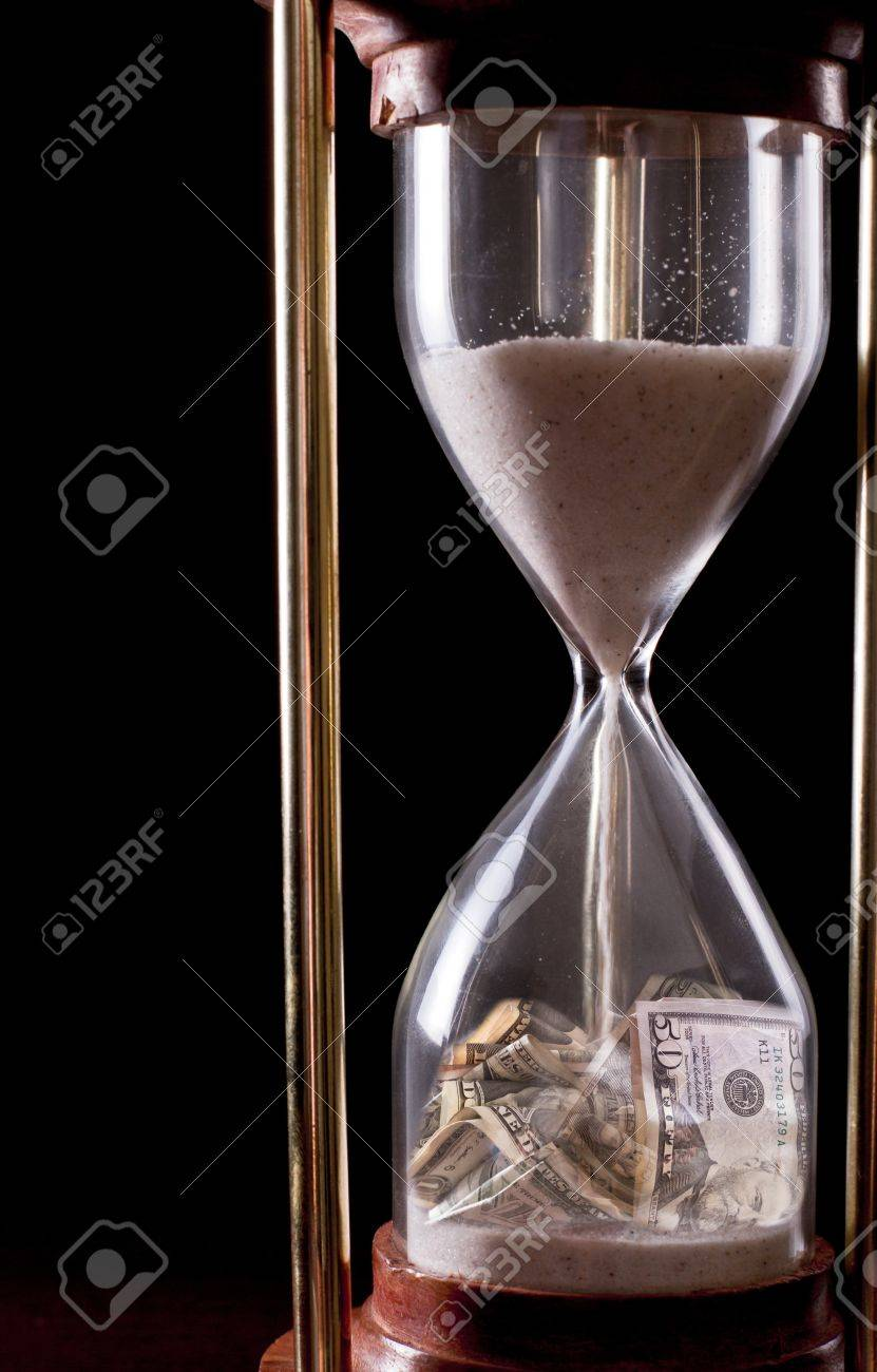 hour glass on a dark background with american money in it Stock Photo - 17445911