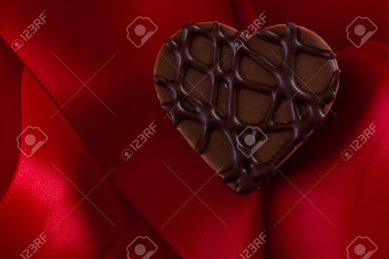 almond cream heart shaped chocolate on a red silk Stock Photo - 17445891
